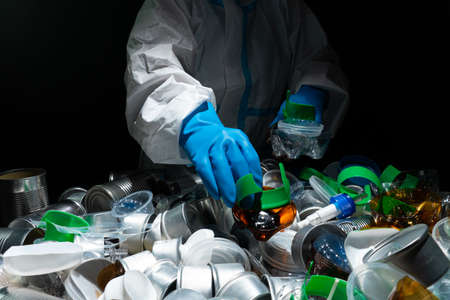 Recycle worker in gloves, sorting one time used plastic bottles and tin metal cans in the trash. Depiction of recycle plant facility. Plastic garbage overproduces and harm to environment. Standard-Bild