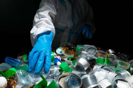 Volunteer cleaning, sorting pile of plastic and metal tin. Collecting, separating one time use plastic trash from aluminum cans. Pollution and environmental problem with household waste management. Standard-Bild