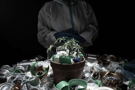 Environmentalist in protective suit holding young seedling in pot full of plastic dirt trash. Concept and symbol of catastrophic apocalypse, eco sustainability, growth care, protecting the earth.