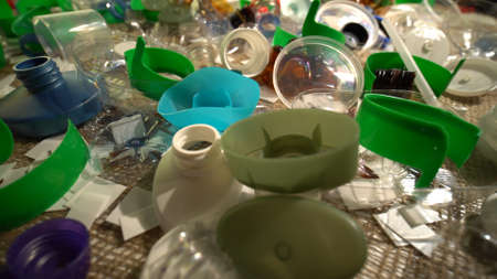 Plastic bottles parts, cups, corks, straws, water and shampoo bottles, creams packaging and other one-time use garbage dumped on the table. Environmental pollution, recycle, waste management problem.