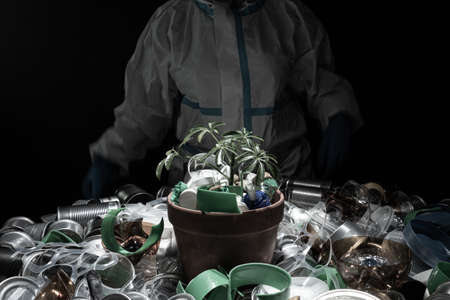 Young seedling in pot full of plastic dirt trash. Concept of environmental conservation disaster due overuse of one time plastic and packaging. Green plant in soil or dirt made of plastic garbage.