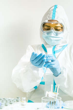 Female doctor or nurse during corona virus pandemic covid-19 prepares to give vaccine. Frontline health care worker in ppe, glasses mask and antiviral suit, put on blue gloves for vaccination.