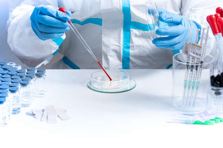 Medical laboratory with equipment and Microbiology scientist wearing ppe scrubs, face shield mask, works with Petri dishes pipette, various tissue and blood samples. Develop vaccine, drugs research. Stockfoto
