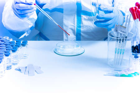 Medical laboratory with equipment and Microbiology scientist wearing ppe scrubs, face shield mask, works with Petri dishes pipette, various tissue and blood samples. Develop vaccine, drugs research. Banco de Imagens