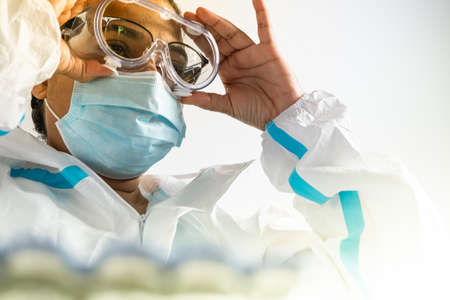 Female doctor or nurse in hospital laboratory during coronavirus pandemic covid-19. Frontline health care worker in ppe, glasses and mask put on medical scrub. Health care practitioner. Banco de Imagens