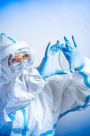 Female microbiologist or lab bio technician holding glass microscope slides with blood positive new strain or mutation Coronavirus. New variant found, new COVID-19 pandemic wave.