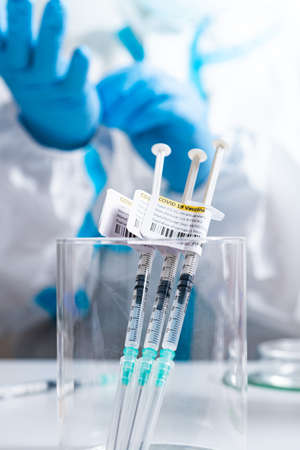 Focus on vaccine against Coronavirus COVID-19. Syringes label in the medical cup with antivirus on the medical worker table. Cure from respiratory syndrome strain of Corona virus. Ready to use shot.