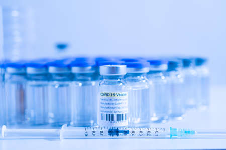 Vaccine vials and syringes containing COVID 19 cure. Ready to administer the shot. Medical research against Coronavirus. Drugs, medications and ppe on the table of medical worker. Banco de Imagens