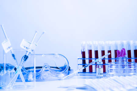 Glass bottle vial and syringe with Covid-19 Coronavirus vaccine in a research medical facility lab. Ampoules with cure on the medical worker laboratory table. Sars-cov-2 pandemic concept. Banco de Imagens