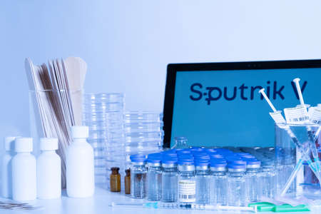 Toronto, Ontario, Canada – April 20, 2021 : Sputnik V vaccine name in blur. Glass vials and syringes with Russian vaccine. Research for Coronavirus COVID-19 cure. Clinical evaluation.