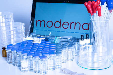 Toronto, Ontario, Canada - February 14, 2021 : A health worker table with shots of the American USA Moderna vaccine. Name on the screen, vials and syringes containing messenger mRNA technology vaccine