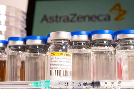 Toronto, Ontario, Canada – April 20, 2021 : AstraZeneca name in blur and vials with syringes containing vaccine. British Swedish Covid-19 vaccine concept. Shallow depth of field view.