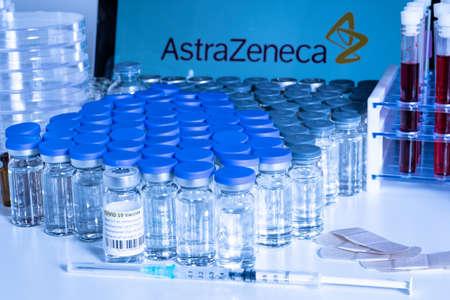 Toronto, Ontario, Canada - April 20, 2021 : AstraZeneca name in blur and vaccine vials containing COVID 19 vaccine. British Swedish Covid-19 vaccine concept. Shallow depth of field view focus.