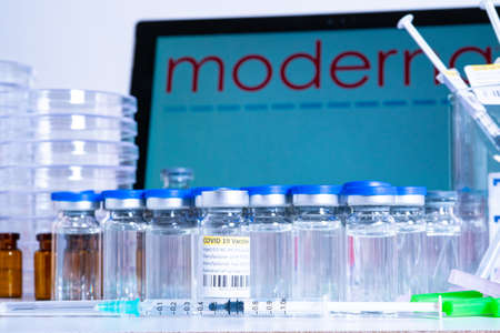 Toronto, Ontario, Canada – April 20, 2021 : Moderna vaccine name in blur and vials with syringes containing cure. American USA Coronavirus Covid-19 vaccine concept. Shallow depth of field.