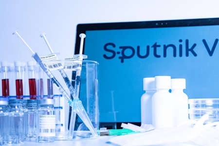 Toronto, Ontario, Canada - April 20, 2021 : Sputnik V vaccine name in blur and vials with syringes containing Gam-COVID-Vac. Russian Coronavirus vaccine concept. Shallow depth of field. Redactioneel