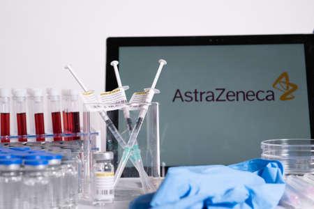 Toronto, Ontario, Canada - April 20, 2021 : AstraZeneca name in blur, vials and syringes containing vaccine on the nurse table. British Swedish Coronavirus vaccine concept. Shallow depth of field.