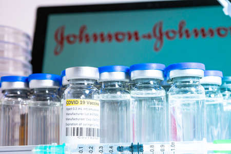 Toronto, Ontario, Canada - April 20, 2021 : Johnson and Johnson name in blur and vials with syringes containing vaccine. American USA Covid-19 vaccine concept. Medical research. Shallow depth of field