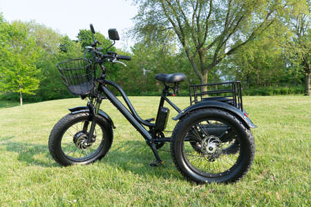 Electric trike or e bicycle in the park in sunny summer day. Shot from the side. A lot of lighting. The view of the e motor and power battery of the three wheel bike.