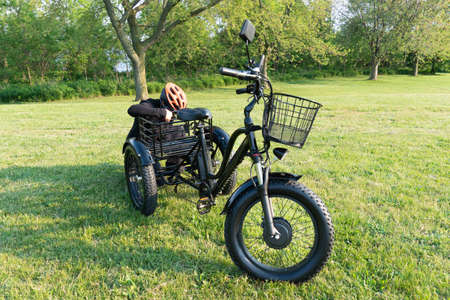 Woman in the hamlet hold the key of the electric bicycle battery pack. Female switch on the powered e bike with the key in the park in sunny summer day. The view of the e bike motor.