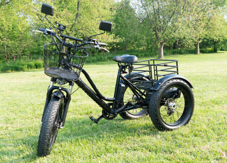 Front wheel side of the electric bicycle, view in sunny summer day in the  green grass. E bike motor with battery. Ecology and green energy concept. Ev – electric vehicle.