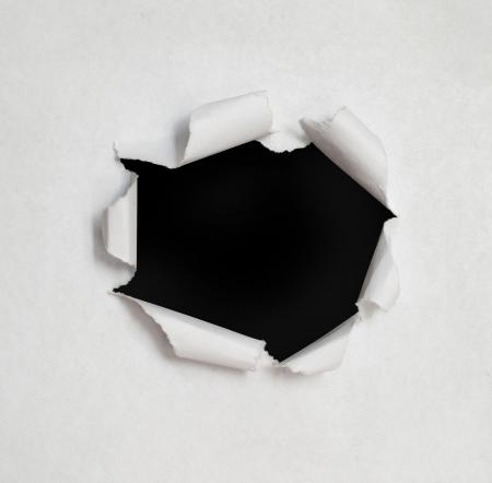papel quemado: Agujero en el papel con lados desgarrados. Foto de archivo