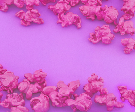Pink popcorn on purple paper background. Fashion pop art style. Top view.