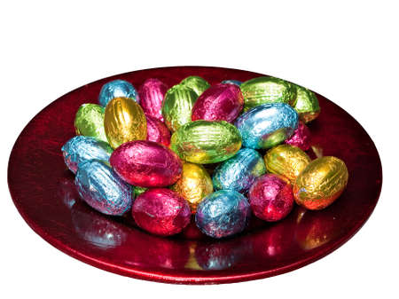 Easter eggs in foil on shiny plate - isolated photo
