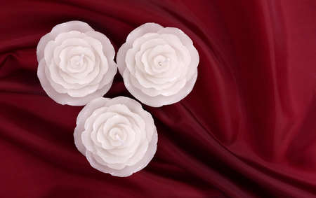 White wax rose candles on red satin photo