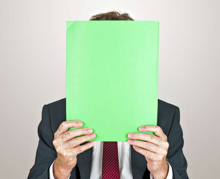 Businessman hiding behind file Stock Photo - 10542789