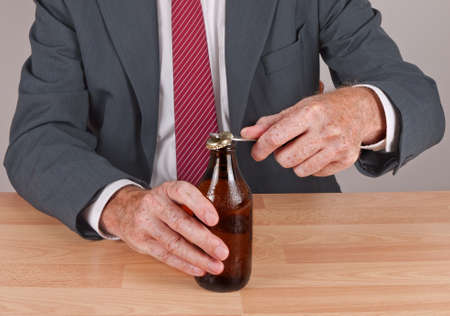beer and necktie: Businessman in suit opening cold beer at desk