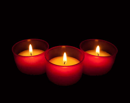 votive: Three candles in red holders over black