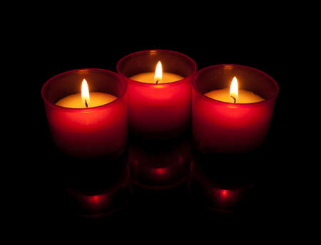 Votive candles in red holder with reflections