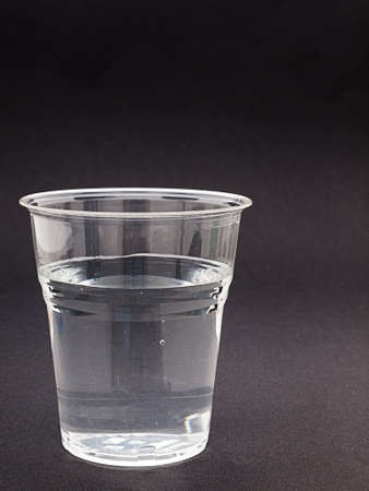 scarce resources: Glass of water over grey gradiant