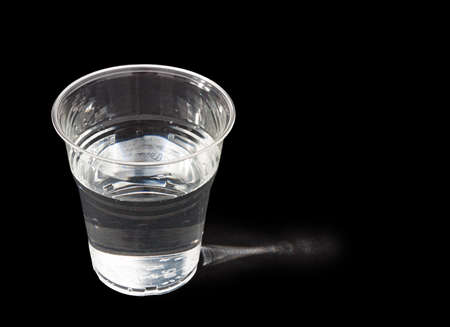 sidelit: Glass of drinking water over black, sidelit