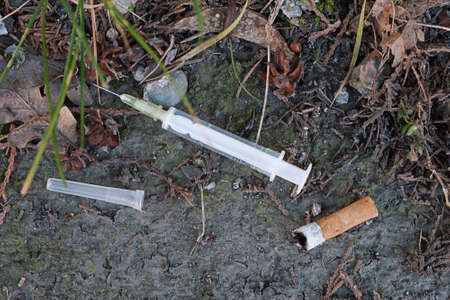 discarded: Discarded syringe in street gutter Stock Photo