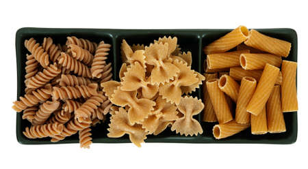 Assorted wholemeal healthy pasta shapes, isolated over white background photo