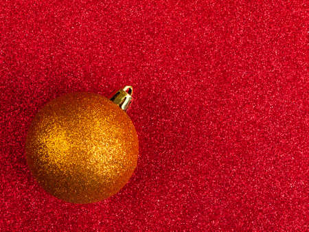 Glittery golden bauble over glitter background - Christmas, festive photo