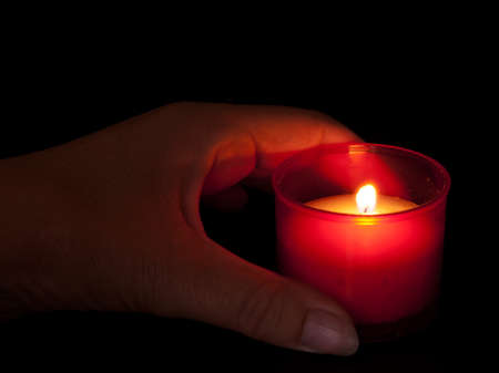 votive: Votive candle with hand, natural candlight for All Saints Day etc Stock Photo
