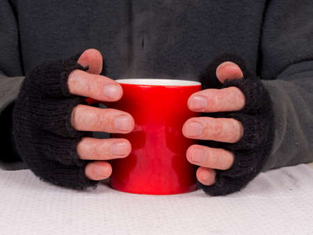homelessness: Poverty - poor man with steaming cup of soup or tea Stock Photo