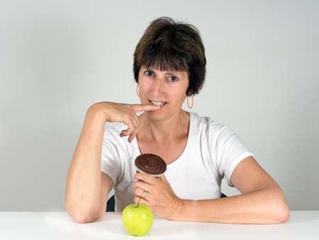 decide: Mujer de mediana edad de decidir sobre la torta de chocolate