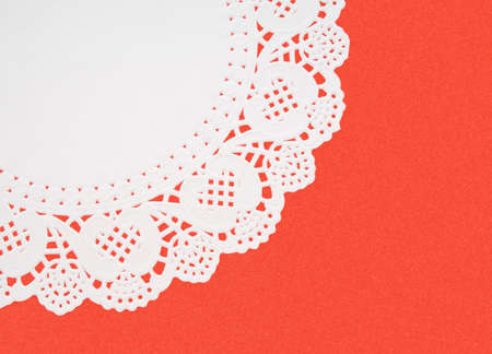 doiley: White embossed doily on red textured background