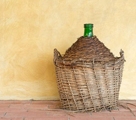 carboy: old wine jar, demijohn, carboy by yellow wall Stock Photo