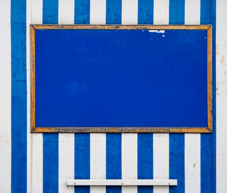 bedraggled: Horizontal old notice board, holiday resort style, blue and white stripes Stock Photo