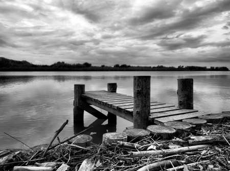 glowering: Wintry, desolate abandoned jetty. Landscape, monochrome.
