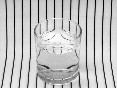 Glass of water on striped cloth. Refraction.