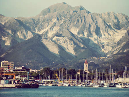 pleasure craft: Carrara marble quarries viewed from offshore. Retro filtered. Stock Photo