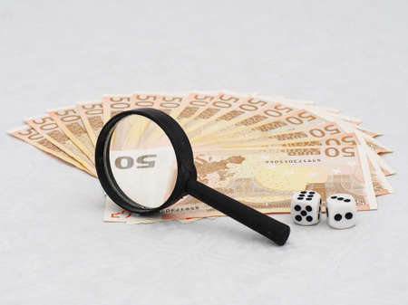 scrutiny: Euro currency under scrutiny. Real magnifying glass and magnification..