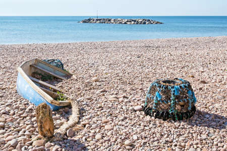 lobster pot: Fishermen no more. Abandoned smallboat and lobster pot on beach