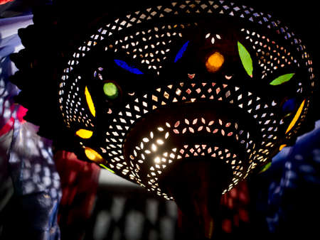 indoors: Moroccan lamp indoors. Hints at interior behind.