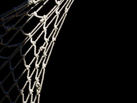 Sunlit fishing net, black background.